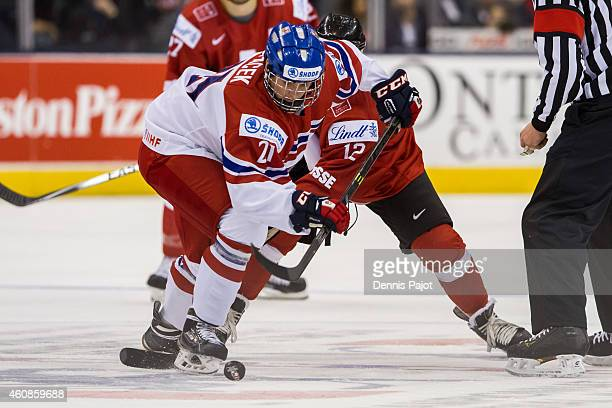 Michael Spacek of Czech Republic battles for the puck on a faceoff against Jason Fuchs of Switzerland during the 2015 IIHF World Junior Championship...