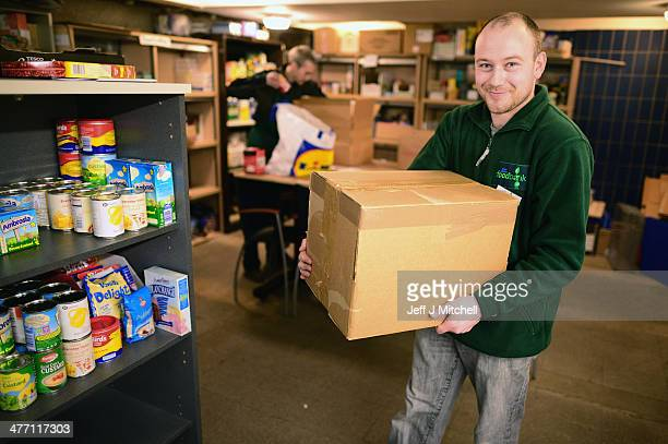 Michael Spence a volunteer packs food at a food bank on March 7 2014 in Whitburn Scotland Charities based in Scotland are reporting that many...