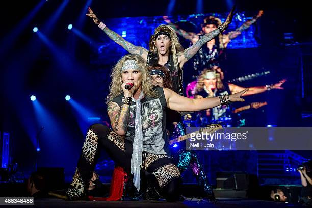 Michael Starr Satchel and Lexxi Foxxx of Steel Panther perform on stage at Wembley Arena on March 14 2015 in London United Kingdom