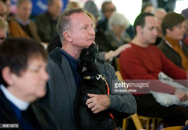 Michael Steingraber who is HIV positive holds his dog Koko during a prayer at a World AIDS Day ceremony at the National AIDS Memorial Grove on...