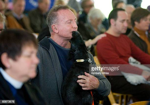 Michael Steingraber who is HIV positive is kissed by his dog Koko during a prayer at a World AIDS Day ceremony at the National AIDS Memorial Grove on...
