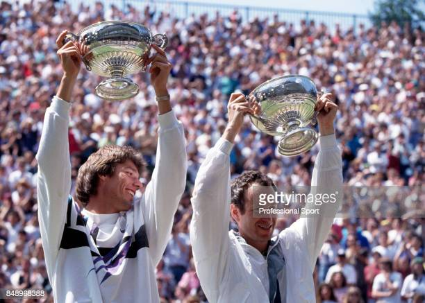 Michael Stich of Germany and John McEnroe of the USA hold their trophies aloft after their victory in the men's doubles final at the Wimbledon Lawn...