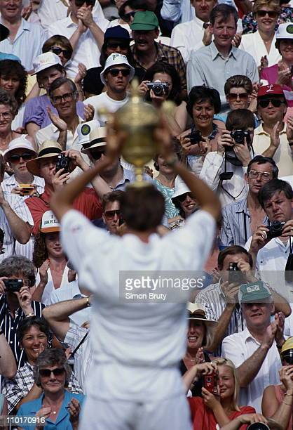 Michael Stich of Germany holds aloft the trophy in triumph to the applauding spectators after defeating Boris Becker during their Men's Singles final...