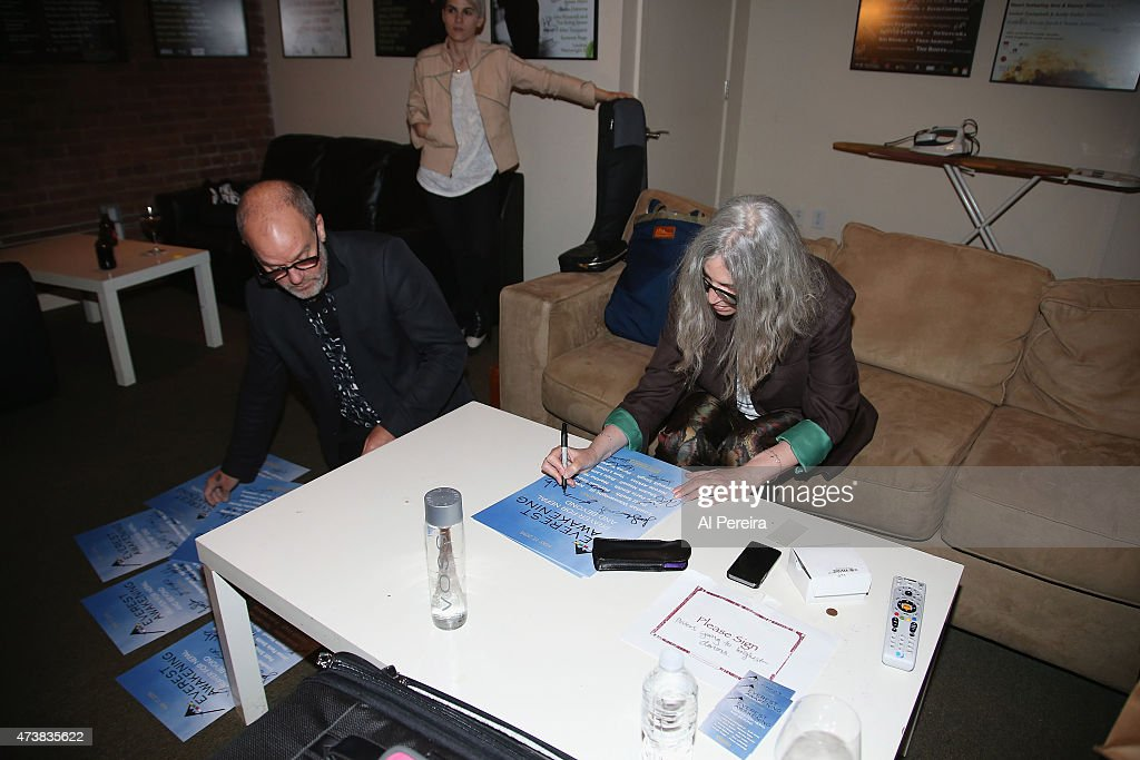 Michael Stipe and Patti Smith autograph posters in the green room for auction after they perform at the Everest Awakening: A Prayer for Nepal and Beyond Benefit show at City Winery on May 17, 2015 in New York City.