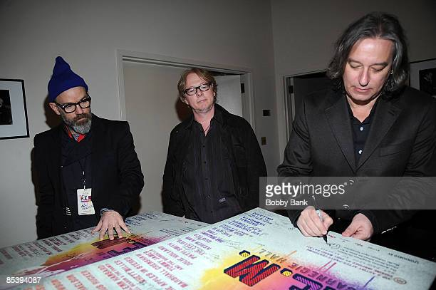 Michael Stipe Mike Mills and Peter Buck of REM sign posters during rehearsals for the Music of REM tribute at Carnegie Hall on March 11 2009 in New...