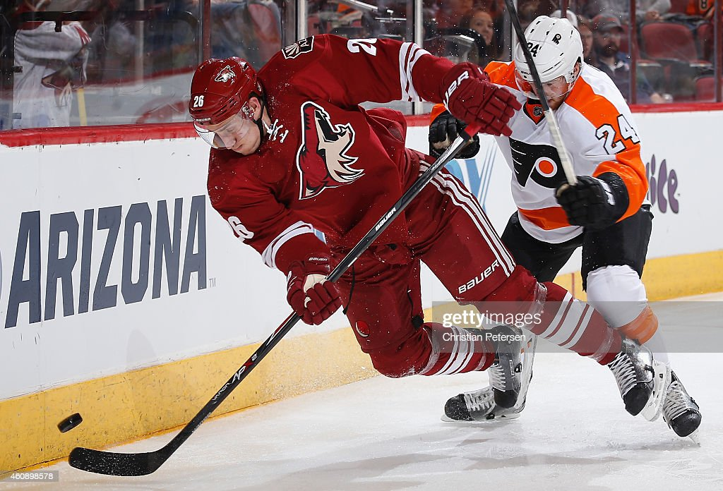 Michael Stone #26 of the Arizona Coyotes is checked off the puck from Matt Read #24 of the Philadelphia Flyers during the second period of the NHL game at Gila River Arena on December 29, 2014 in Glendale, Arizona.