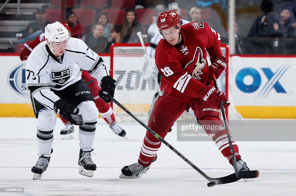 Michael Stone #26 of the Arizona Coyotes skates after the puck under pressure from Tyler Toffoli #73 of the Los Angeles Kings during the third period of the NHL game at Gila River Arena on December 4, 2014 in Glendale, Arizona. The Kings defeated the Coyotes 4-0.