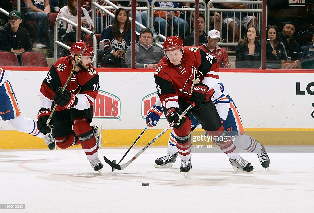 Michael Stone #26 of the Arizona Coyotes skates with the puck next to teammate Brad Richardson #12 as Taylor Hall #4 of the Edmonton Oilers trails the play during the third period at Gila River Arena on November 12, 2015 in Glendale, Arizona.