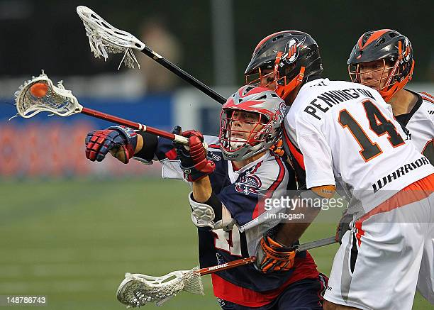 Michael Stone of the Boston Cannons feels the pressure of Justin Pennington and Dillon Roy of the Denver Outlaws at Harvard Stadium July 19 2012 in...