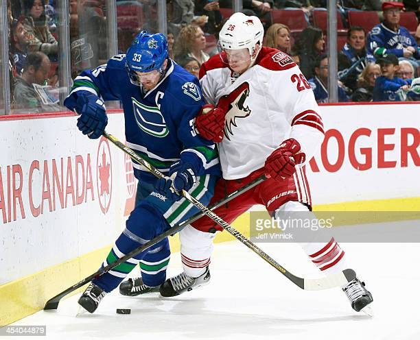 Michael Stone of the Phoenix Coyotes checks Henrik Sedin of the Vancouver Canucks during their NHL game at Rogers Arena on December 6 2013 in...