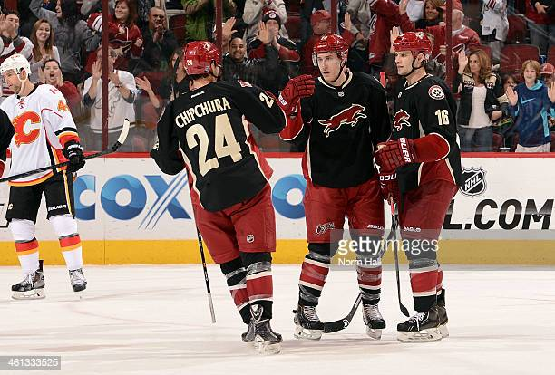Michael Stone of the Phoenix Coyotes is congratulated by teammates Kyle Chipchura and Rostilav Klesla after his third period goal against the Calgary...