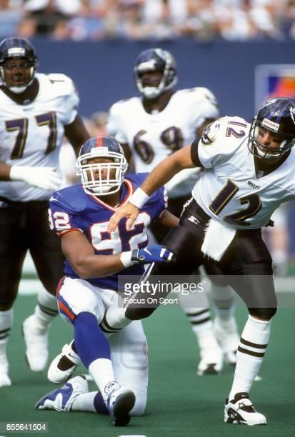 Michael Strahan of the New York Giants puts pressure on quarterback Vinny Testaverde of the Baltimore Ravens during an NFL football game September 14...