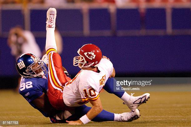 Michael Strahan of the New York Giants tosses Trent Green of the Kansas City Chiefs to the ground on August 13 2004 at Giants Stadium in the East...