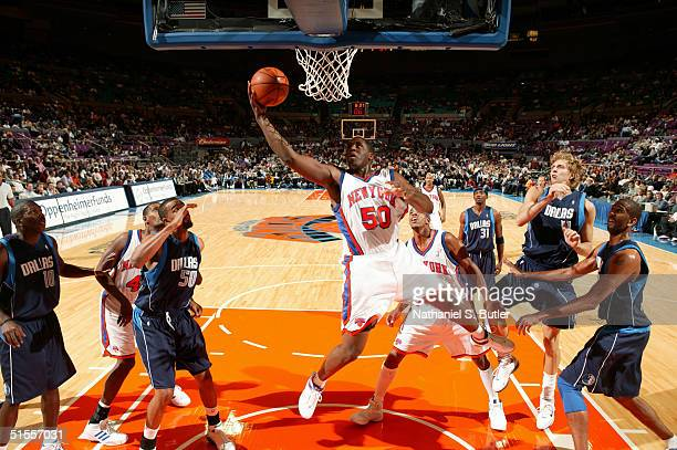 Michael Sweetney of the New York Knicks attempts reverse layup against Alan Henderson of the Dallas Mavericks during preseason on October 24 2004 at...