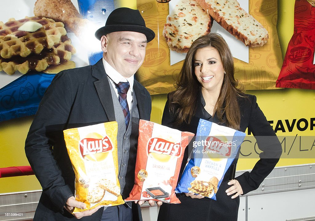 Michael Symon and Eva Longoria pose for a photo for photographers during NYSE Celebrates Lay's 'Do Us a Flavor' Contest Finalists during the opening bell at New York Stock Exchange on February 12, 2013 in New York City.