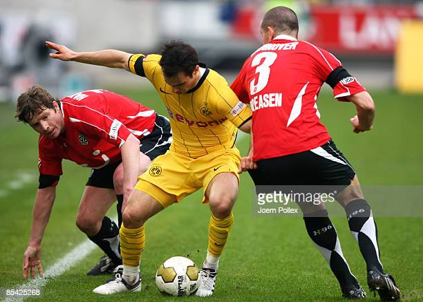 Michael Tarnat and Leon Andreasen of Hannover surrounded Tamas Hajnal of Dortmund and battle for the ball during the Bundesliga match between...