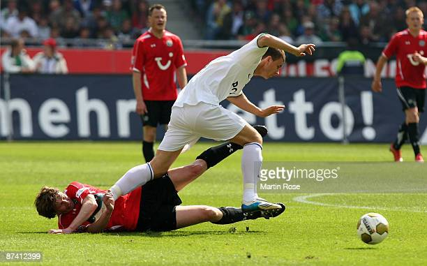 Michael Tarnat of Hannover 96 and Edin Dzeko of Wolfsburg compete for the ball during the Bundesliga match between Hannover 96 and VfL Wolfsburg at...