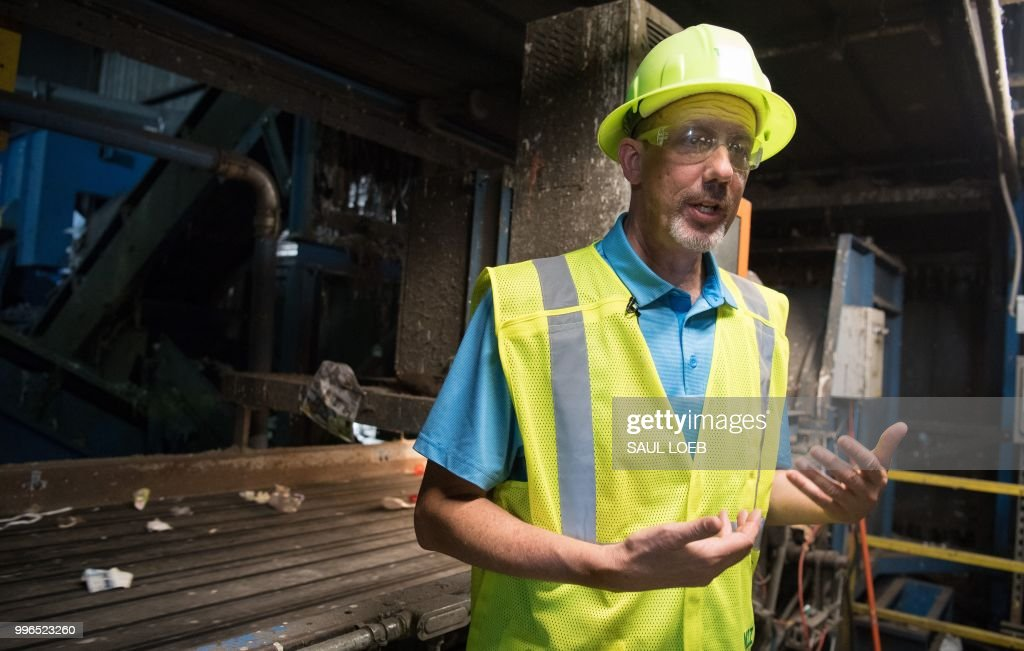 Michael Taylor, director of recycling operations at Waste Management, speaks about recycling material at the Waste Management Material Recovery Facility in Elkridge, Maryland, June 28, 2018. - Some 900 tons of trash are dumped at all hours of the day and night, five days a week, on the conveyor belts at the plant. For months, this major recycling facility for the greater Baltimore-Washington area has been facing a big problem: it has to pay to get rid of huge amounts of paper and plastic it would normally sell to China. But Beijing is no longer buying, claiming the recycled materials are 'contaminated.'
