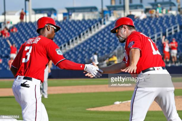 Michael Taylor is congratulated by third base coach Bob Henley of the Washington Nationals after hitting a solo home run against the Houston Astros...
