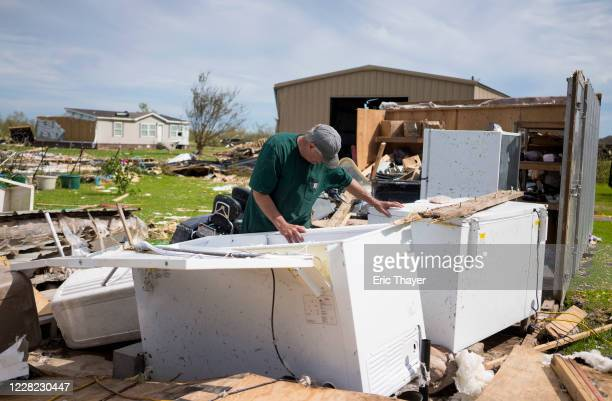 Michael Taylor looks through a freezer damaged by Hurricane Laura August 27, 2020 in Grand Lake, Louisiana. Hurricane Laura came ashore bringing rain...