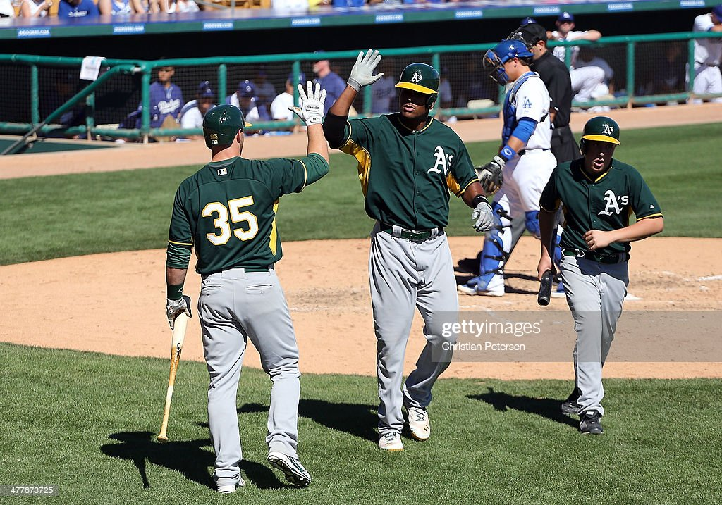 Michael Taylor #23 of the Oakland Athletics high-fives Chris Gimenez #35 after Taylor his a solo home run against the Los Angeles Dodgers during the fifth inning of the spring training game at Camelback Ranch on March 10, 2014 in Glendale, Arizona.