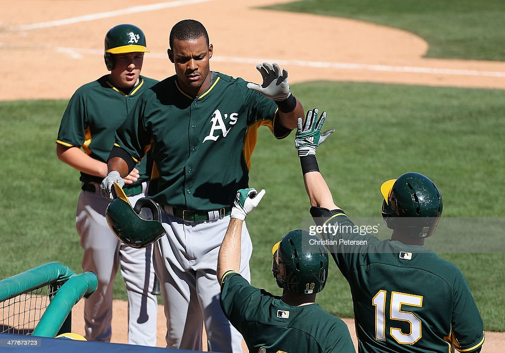 Michael Taylor #23 of the Oakland Athletics high-fives Jake Elmore #15 after Taylor his a solo home run against the Los Angeles Dodgers during the fifth inning of the spring training game at Camelback Ranch on March 10, 2014 in Glendale, Arizona.