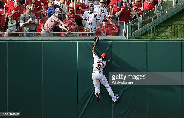Michael Taylor of the Washington Nationals leaps and misses catching a ball hit by Travis d'Arnaud that resulted in a triple in the 7th inning during...