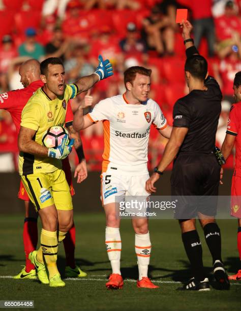 Michael Theo of Brisbane Roar reacts after receiving a red card from referee Stephen Lucas during the round 23 ALeague match between Adelaide United...