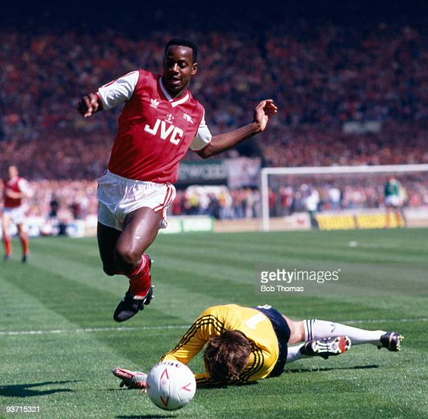 Michael Thomas of Arsenal hurdles Luton Town's goalkeeper Andy Dibble during the Arsenal v Luton Town Littlewoods Cup Final held at Wembley Stadium...