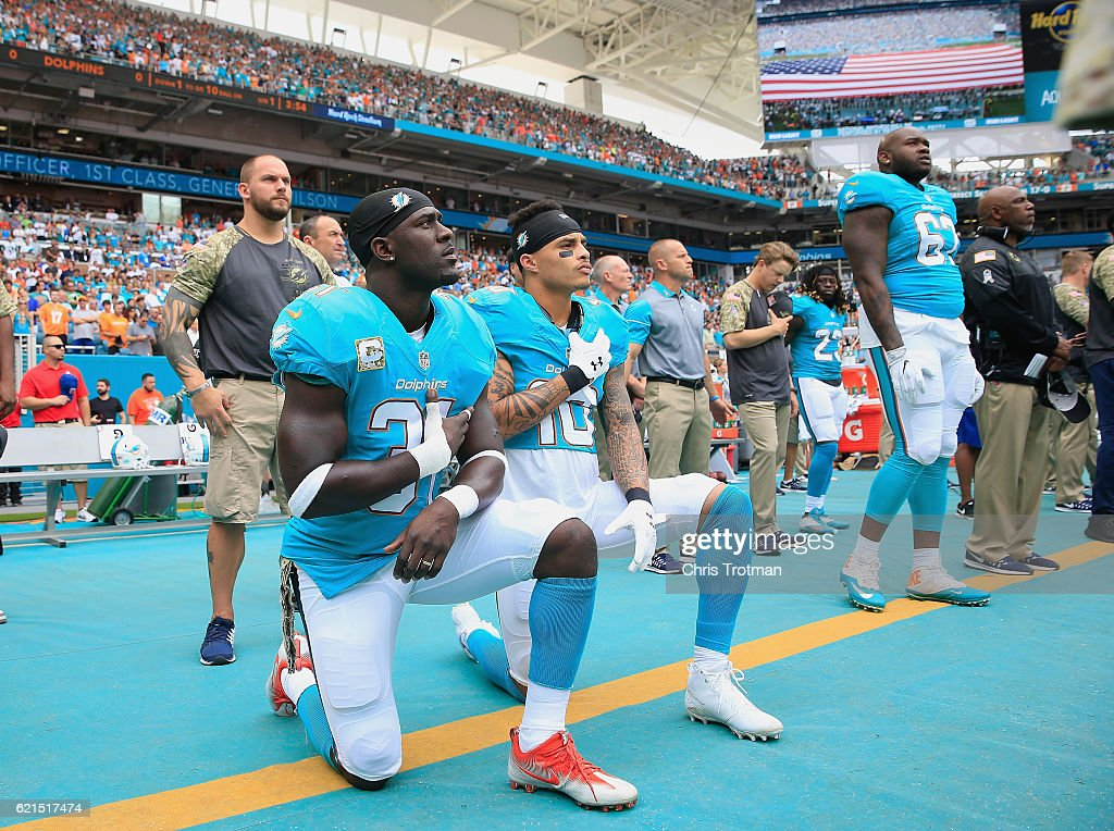Michael Thomas #31 of the Miami Dolphins and Kenny Stills #10 of the Miami Dolphins take a knee during the national anthem prior to the game against the New York Jets at the Hard Rock Stadium on November 6, 2016 in Miami Gardens, Florida.