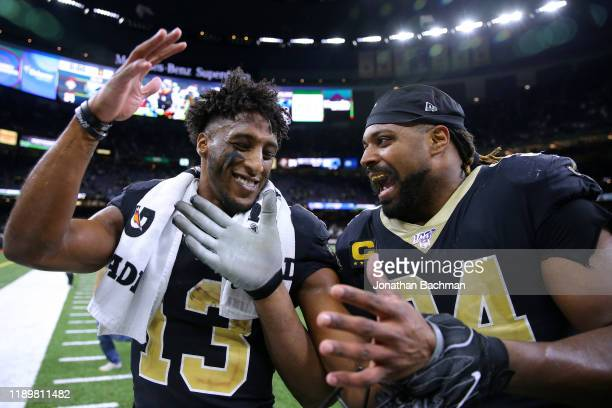 Michael Thomas of the New Orleans Saints and Cameron Jordan celebrate a win against the Carolina Panthers after a game at the Mercedes Benz Superdome...