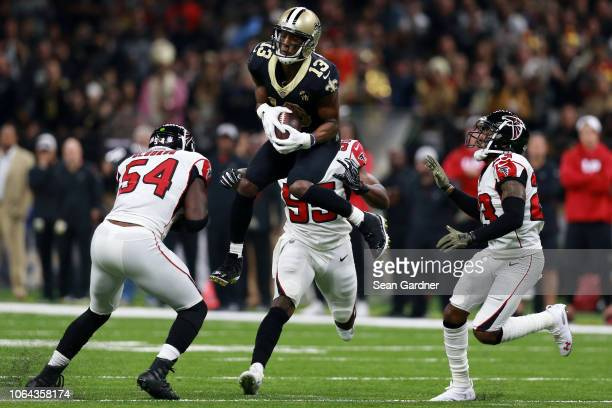 Michael Thomas of the New Orleans Saints catches the ball as Foye Oluokun of the Atlanta Falcons defends during the first half at the MercedesBenz...