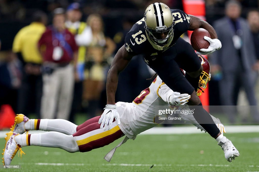 Michael Thomas #13 of the New Orleans Saints is tackled by D.J. Swearinger #36 of the Washington Redskins during the first half at the Mercedes-Benz Superdome on November 19, 2017 in New Orleans, Louisiana.