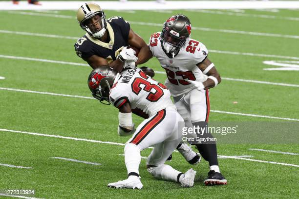 Michael Thomas of the New Orleans Saints is tackled by Jordan Whitehead and Sean Murphy-Bunting of the Tampa Bay Buccaneers during the second quarter...