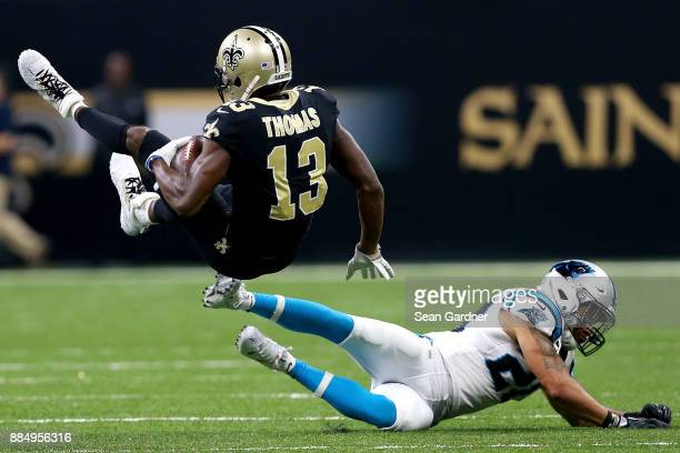Michael Thomas of the New Orleans Saints is tackled by Kurt Coleman of the Carolina Panthers during the first half of a NFL game at the MercedesBenz...