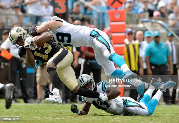Michael Thomas of the New Orleans Saints makes a catch against Luke Kuechly and Captain Munnerlyn of the Carolina Panthers during their game at Bank...