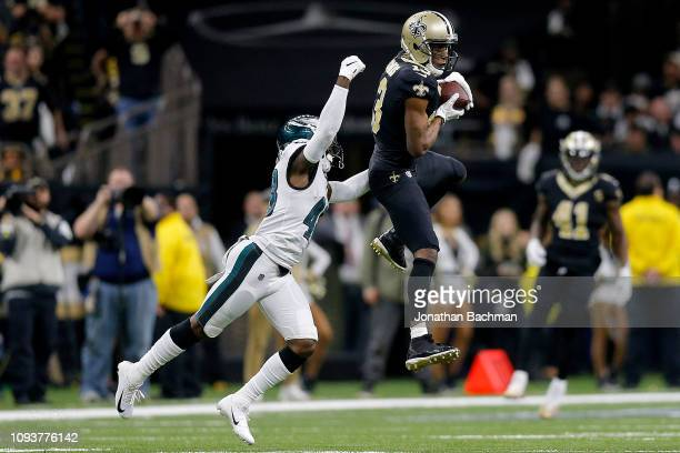 Michael Thomas of the New Orleans Saints makes the catch under pressure from Josh Hawkins of the Philadelphia Eagles during the fourth quarter in the...