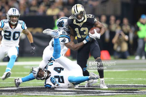 Michael Thomas of the New Orleans Saints runs the ball against Mike Adams and James Bradberry of the Carolina Panthers during the first half of the...