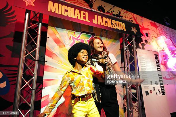 Michael Thurston Australian tourist Ashleigh Porteous poses with a wax figure of Michael Jackson June 22 2011 at a special exhibition marking the...