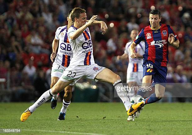 Michael Thwaite of Perth Glory contests the ball with Michael Bridges of te Newcastle jets during the round 24 ALeague match between the Newcastle...