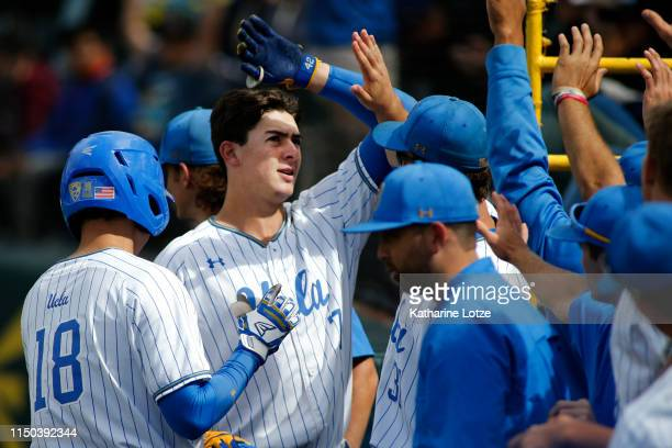 Michael Toglia of UCLA highfives teammates following his home run during a baseball game against University of Washington at Jackie Robinson Stadium...