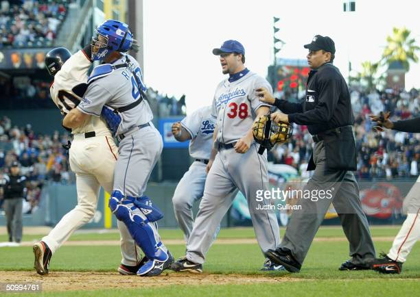 Michael Tucker of the San Francisco Giants is tackled by David Ross the Los Angeles Dodgers as he tried to charge the mound to get to Dodger pitcher...