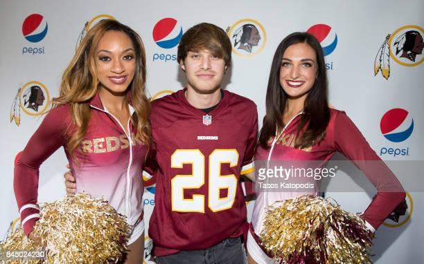 Michael Tyler poses with Washington Redskins cheerleaders at Vanish Brewery on September 9 2017 in Leesburg Virginia