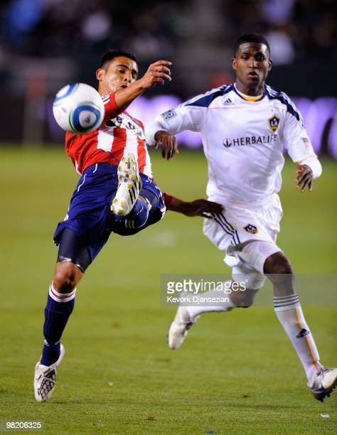 Michael Umana of Chivas USA clears the ball away from Edson Buddle of the Los Angeles Galaxy during the second half of the MLS soccer match on April...