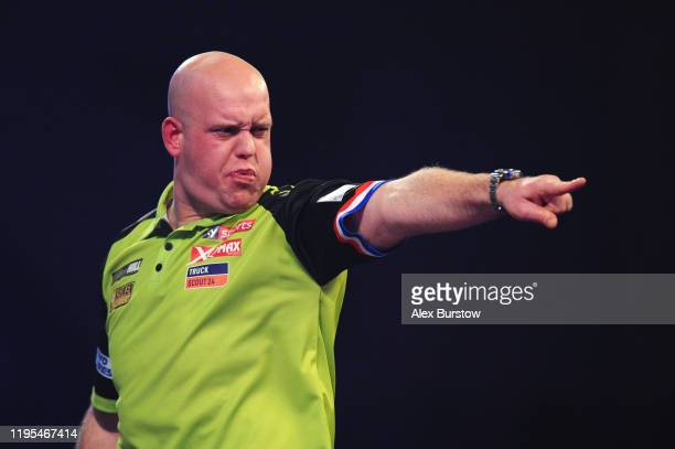 Michael van Gerwen of The Netherlands celebrates after winning the first set in his Third Round Match against Ricky Evans of England during Day Ten...