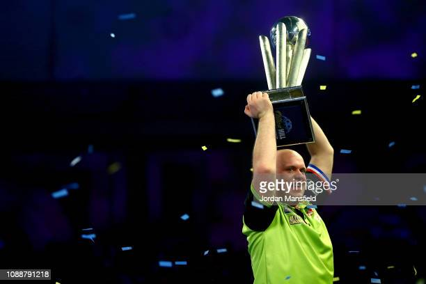 Michael van Gerwen of the Netherlands lifts the trophy after victory in the Final match against Michael Smith of England during Day 17 of the 2019...