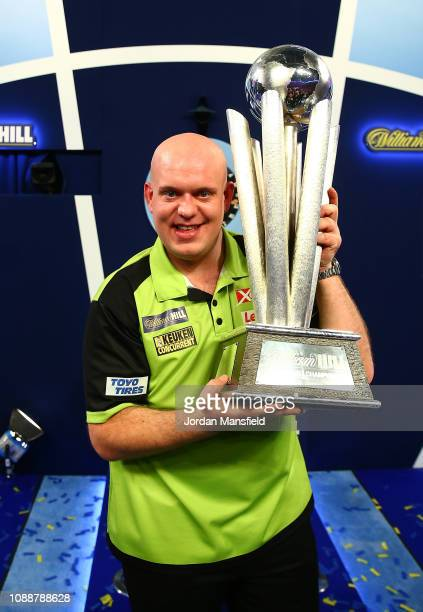 Michael van Gerwen of the Netherlands poses with the trophy after victory in the Final match against Michael Smith of England during Day 17 of the...