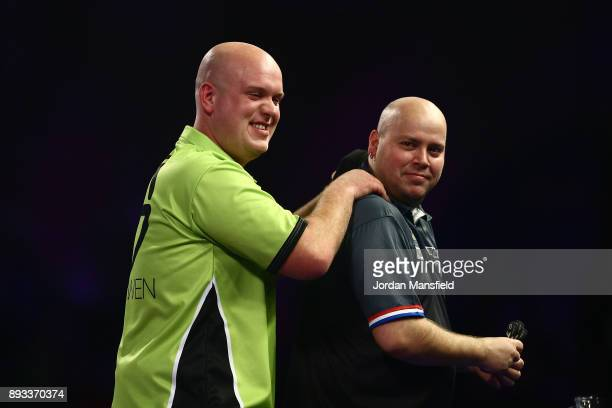 Michael van Gerwen of the Netherlands shakes hands with Christian Kist of the Netherlands after victory in their first round match on day one of the...