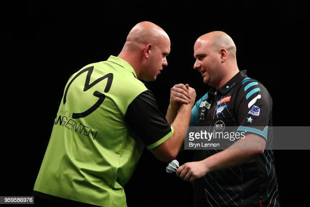 Michael van Gerwen of The Netherlands shakes hands with Rob Cross of Great Britain after winning their semifinal at the Betway Premier League Darts...