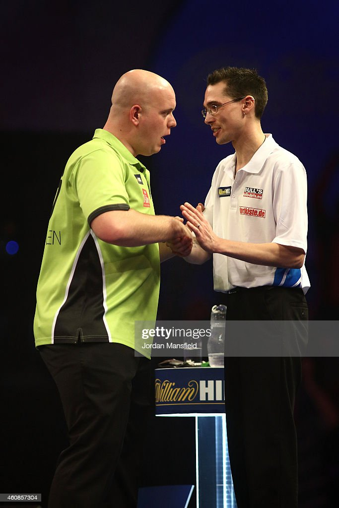 Michael van Gerwen of the Netherlands shakes hands with Sascha Stein of Germany after their second round match on Day Seven of the William Hill PDC World Darts Championships at Alexandra Palace on December 27, 2014 in London, England.